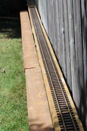 g scale track attached to fence